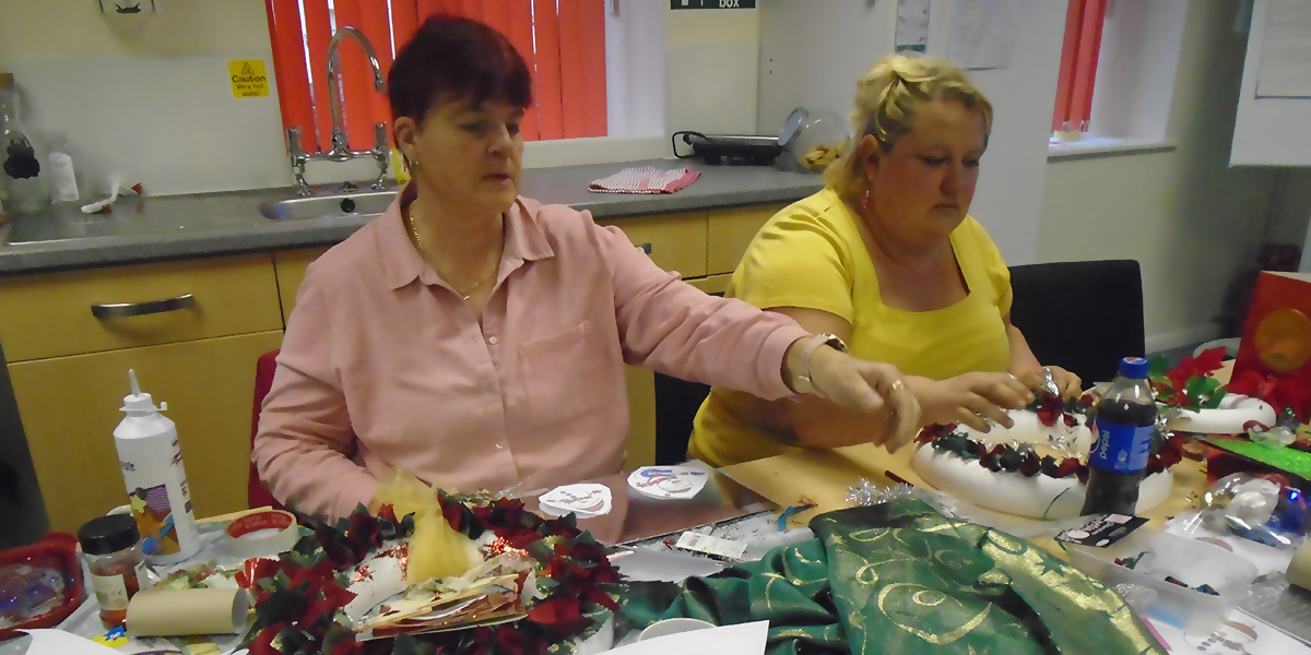 Photo of two ladies busy making Christmas decorations