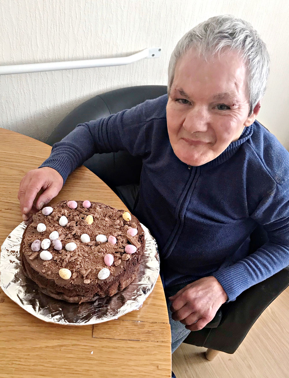 Ian sitting at a table with his finished cake on a silver paper tray.