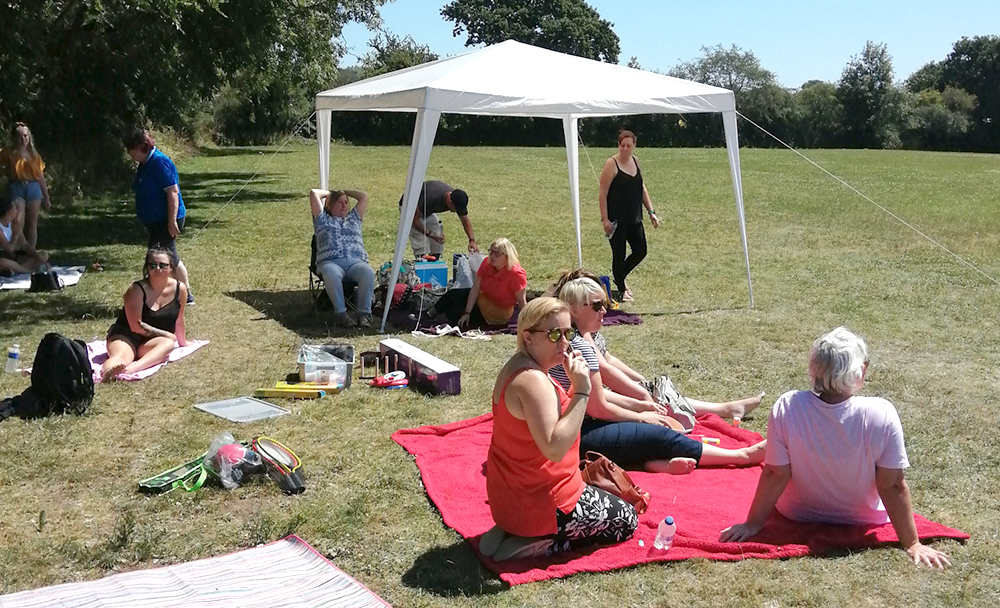 Some people are enjoying the shade under the gazebo in the park
