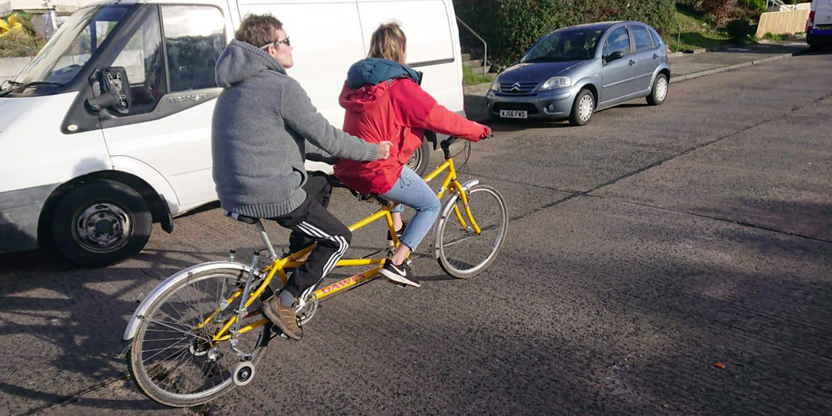 Photo of Ricky and his support worker riding a tandem.